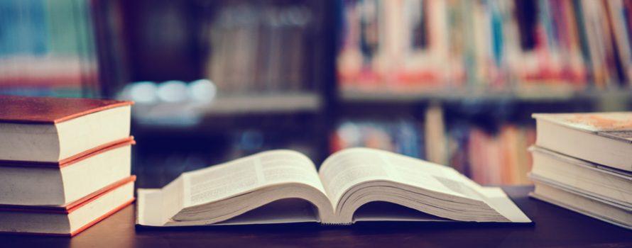 książka otwarta na biurku, biblioteka w tle